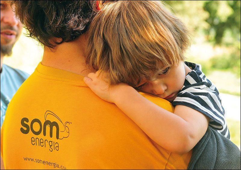 Home amb samarreta de Som Energia agafant un nen en braços